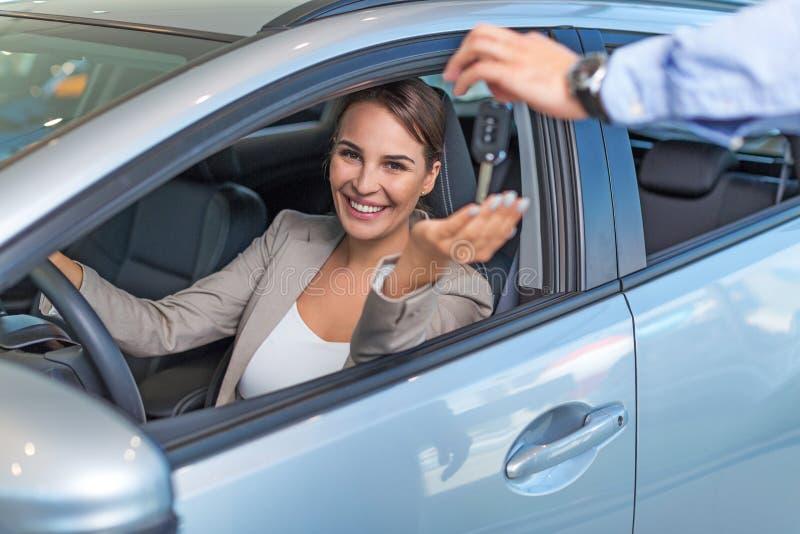 Giovane donna con la sua nuova automobile fotografia stock