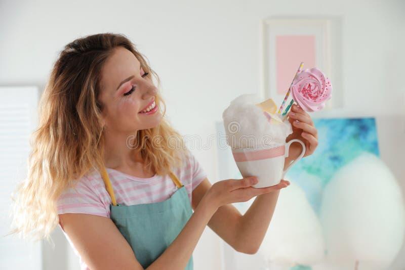 Giovane donna con la tazza del dessert dello zucchero filato immagine stock libera da diritti