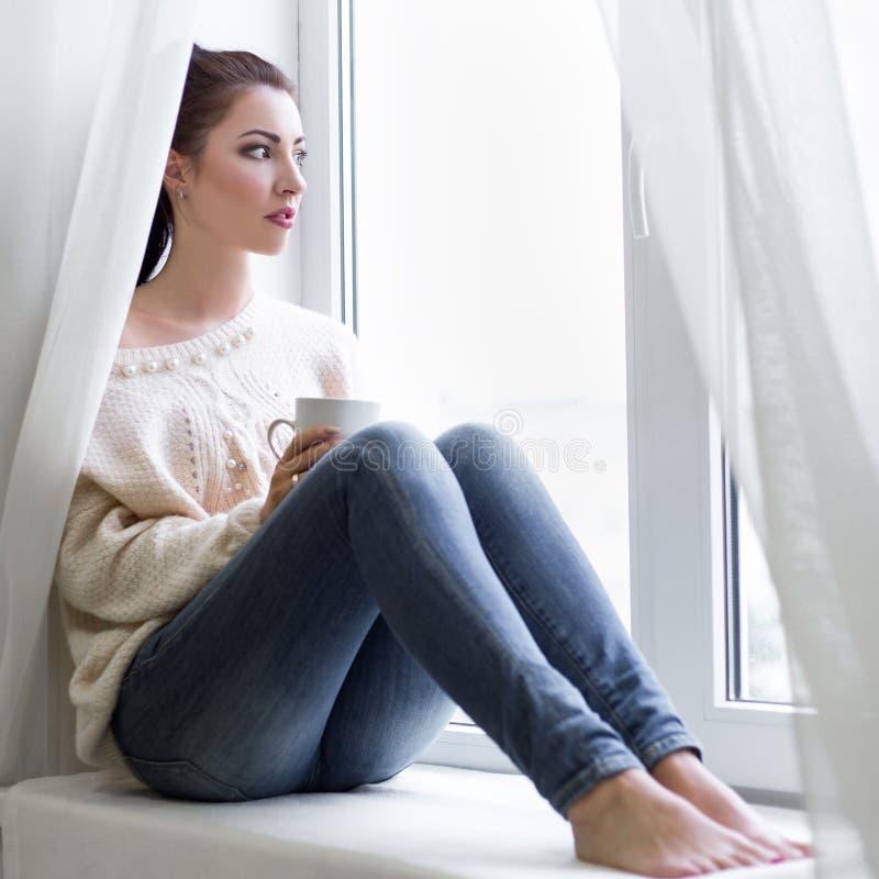 Giovane donna con la tazza di caffè che guarda dalla finestra immagini stock