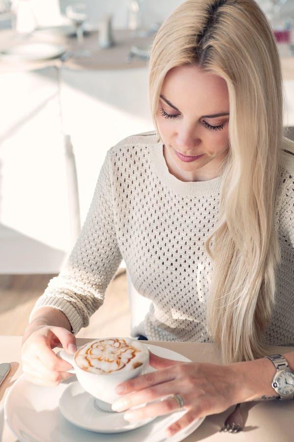 Giovane donna con la tazza di coffe in ristorante fotografia stock