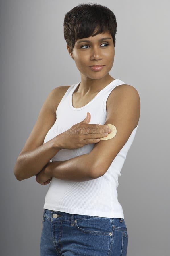 Giovane donna con la toppa del nicotina sul braccio fotografie stock