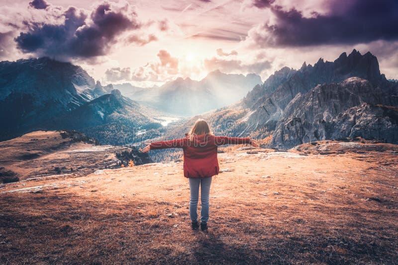 Giovane donna con le armi su alzate e montagne al tramonto immagini stock