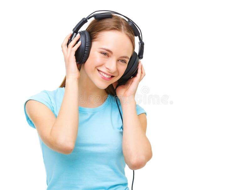 Giovane donna con le cuffie che ascolta la musica e ballare fotografia stock