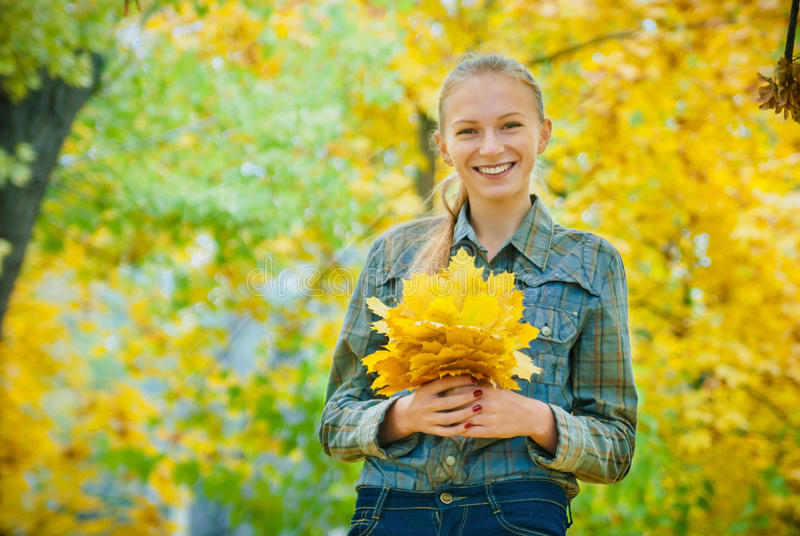 Giovane donna con le foglie di autunno fotografia stock libera da diritti