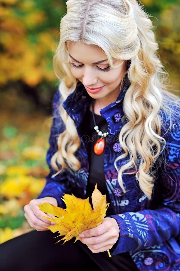 Giovane donna con le foglie di autunno a disposizione ed il luccio giallo dell'acero di caduta fotografie stock