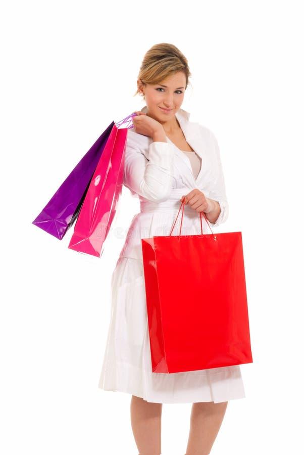 Giovane donna con levarsi in piedi dei sacchetti di acquisto fotografia stock libera da diritti