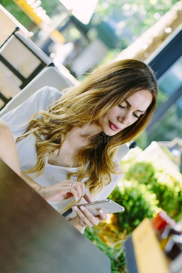 Giovane donna con lo Smart Phone che si siede nel ristorante immagini stock libere da diritti