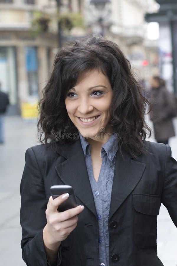 Giovane donna con lo smartphone che cammina sulla via fotografie stock