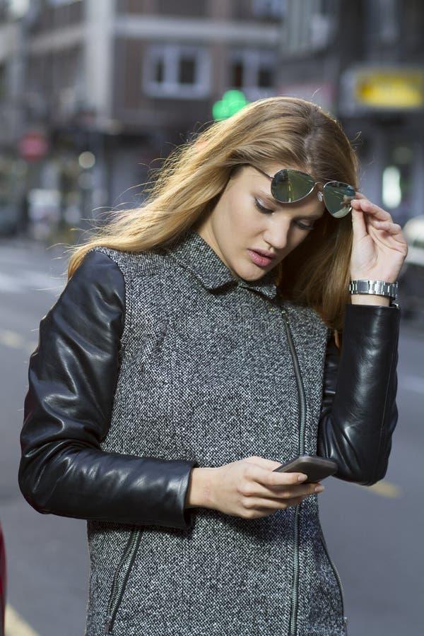 Giovane donna con lo smartphone che cammina sulla via immagine stock