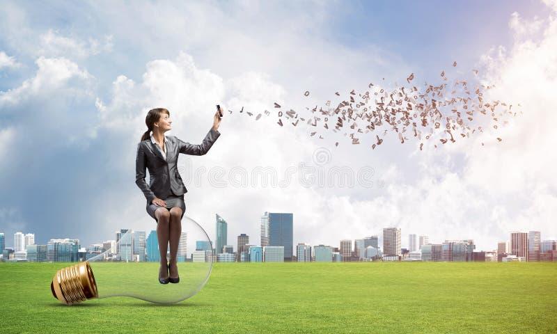 Giovane donna con lo smartphone che invia messaggio di testo fotografia stock