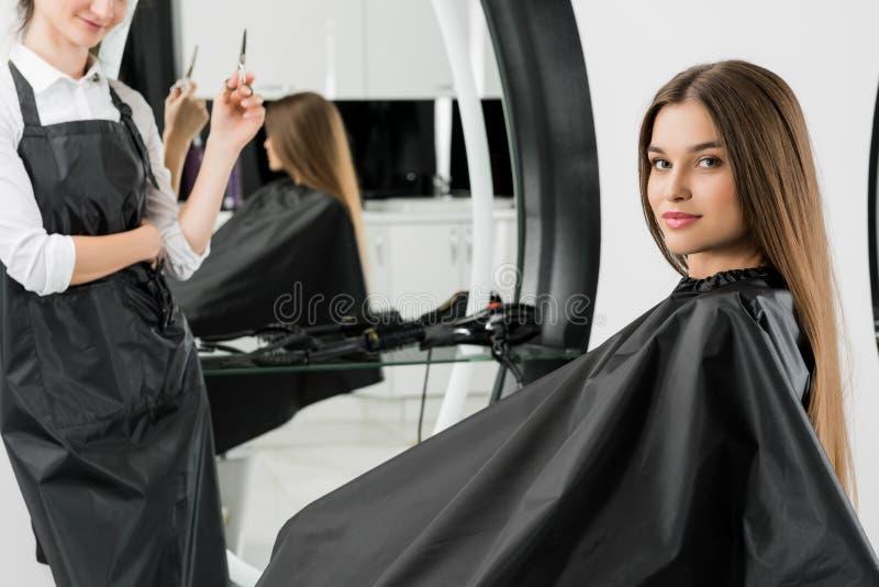 Giovane donna con lo stilista di capelli fotografia stock