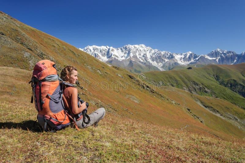 Giovane donna con lo zaino che si siede sulla cima e che guarda alla montagna fotografia stock