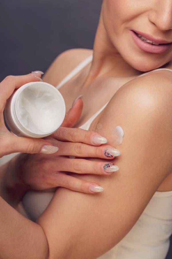 Giovane donna con pelle sana che applica crema cosmetica fotografia stock libera da diritti
