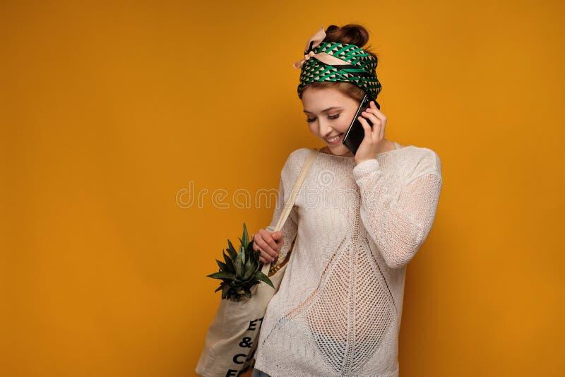 Giovane donna con un ananas nei suoi colloqui del sacchetto della spesa sul telefono sopra fondo giallo fotografia stock libera da diritti