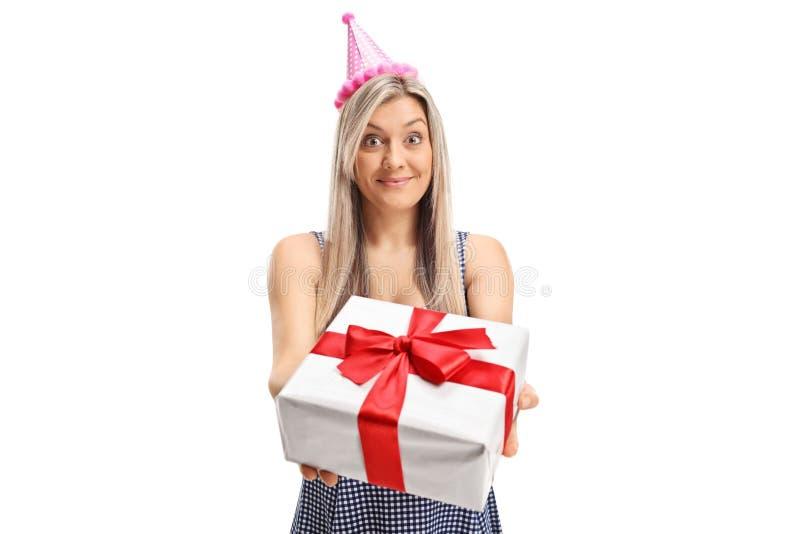 Giovane donna con un cappello del partito che dà un presente immagine stock