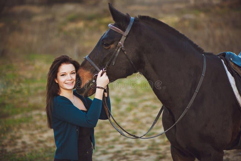Giovane donna con un cavallo sulla natura fotografie stock