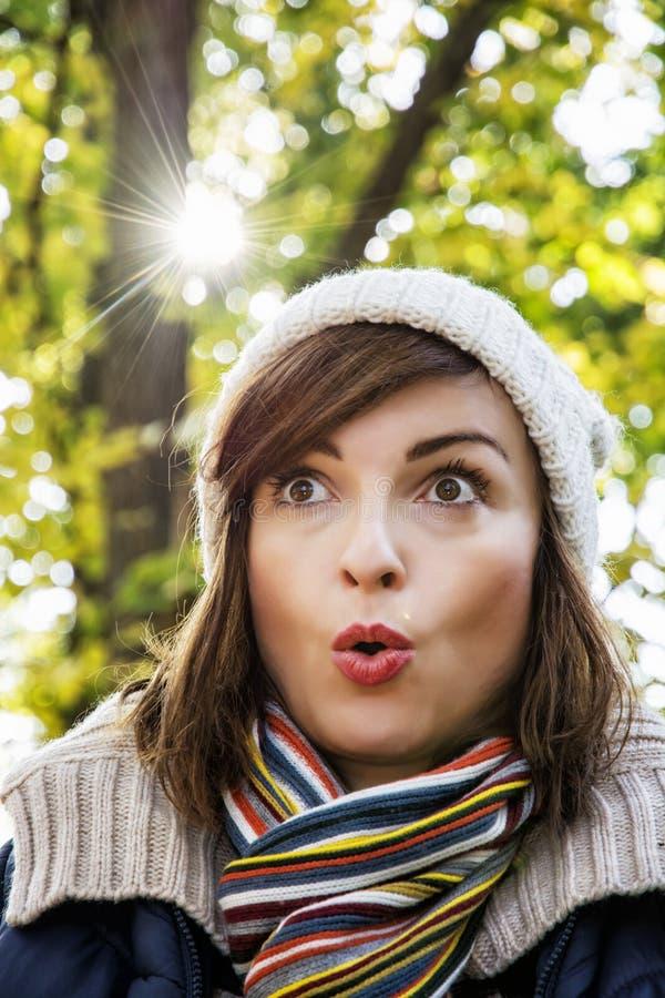 Giovane donna con un'espressione facciale sorpresa nel parco di autunno fotografia stock libera da diritti