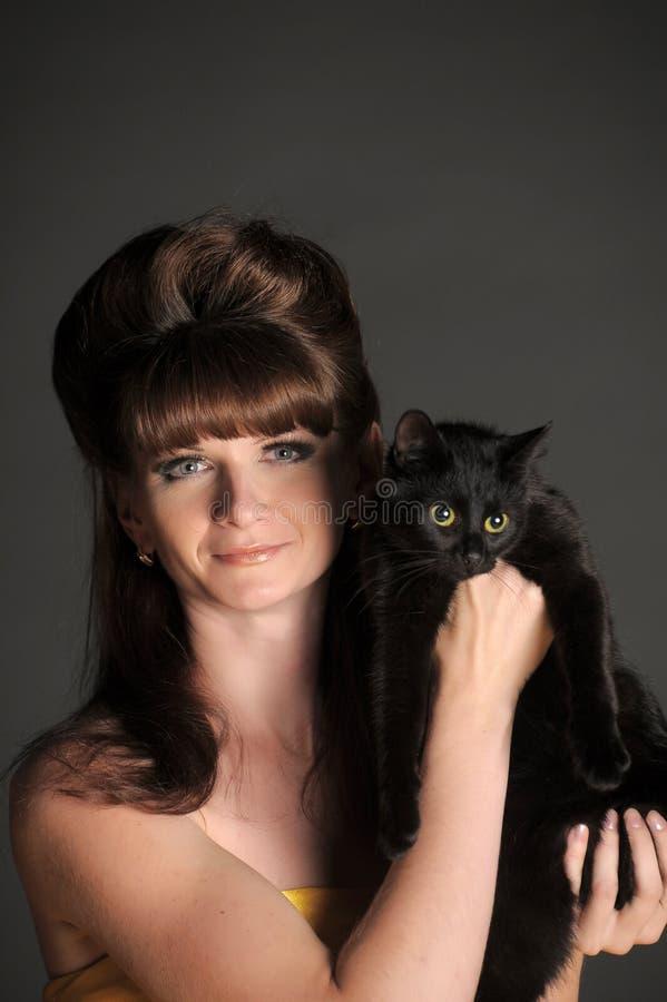 Giovane donna con un gatto nero fotografie stock libere da diritti