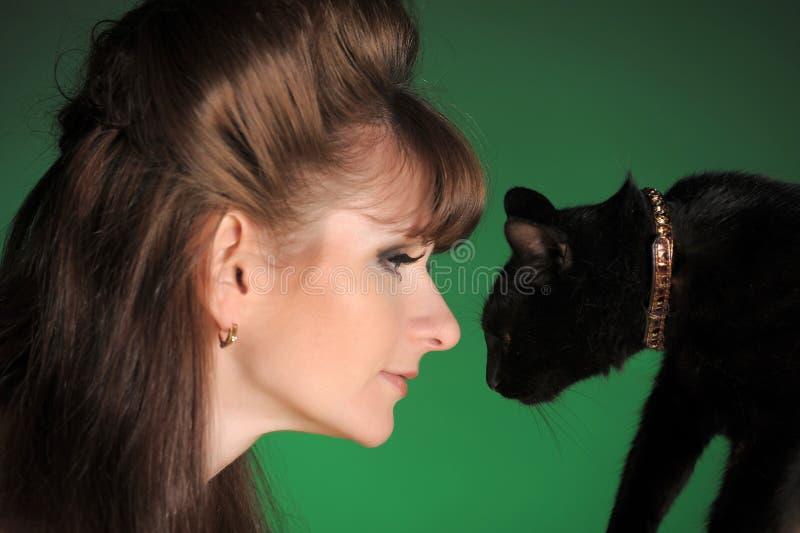 Giovane donna con un gatto nero fotografia stock