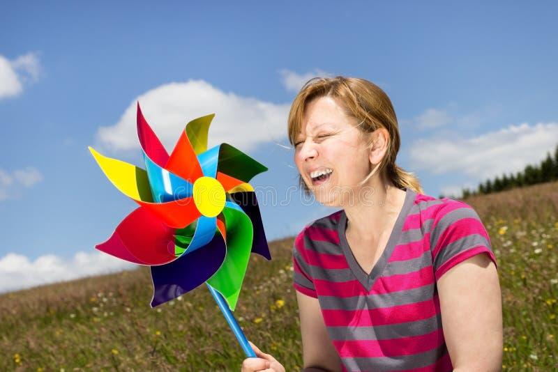Giovane donna con un mulino a vento fotografie stock libere da diritti