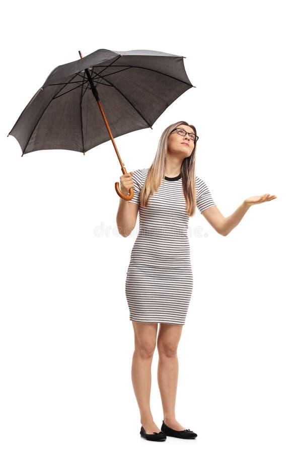 Giovane donna con un ombrello che controlla per vedere se sta piovendo immagini stock