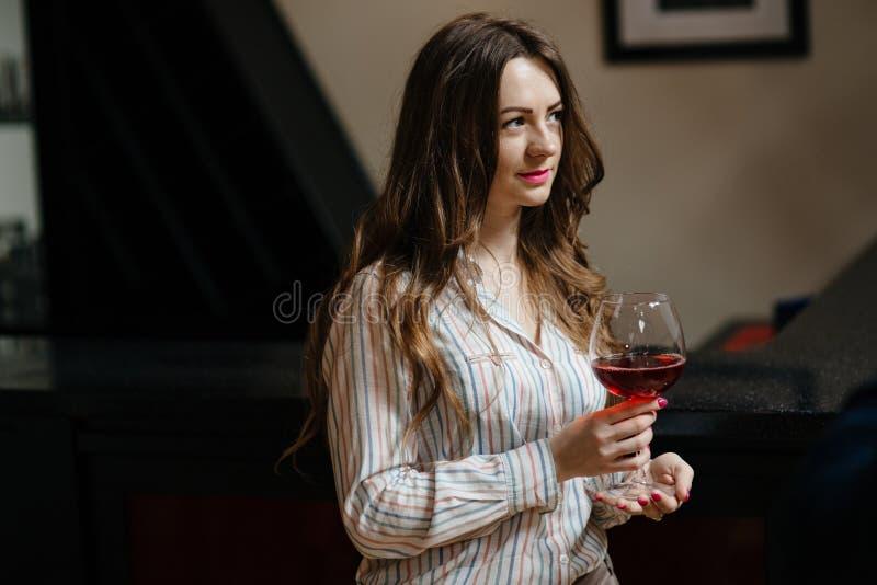 Giovane donna con un vetro di vino fotografia stock libera da diritti