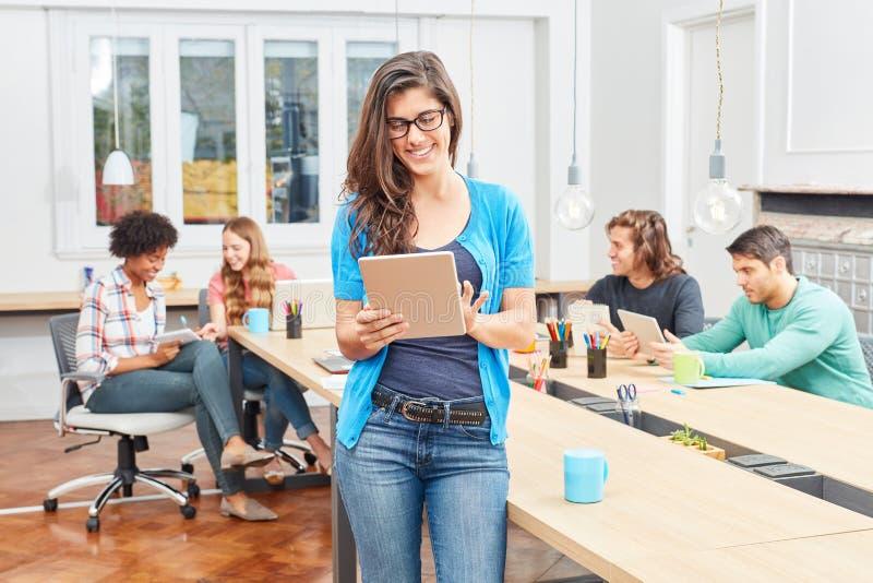 Giovane donna con una compressa in ufficio coworking immagine stock libera da diritti