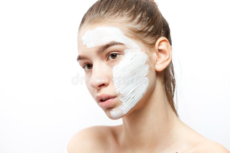 Giovane donna con una maschera cosmetica bianca su una metà del suo fronte sui precedenti bianchi fotografia stock