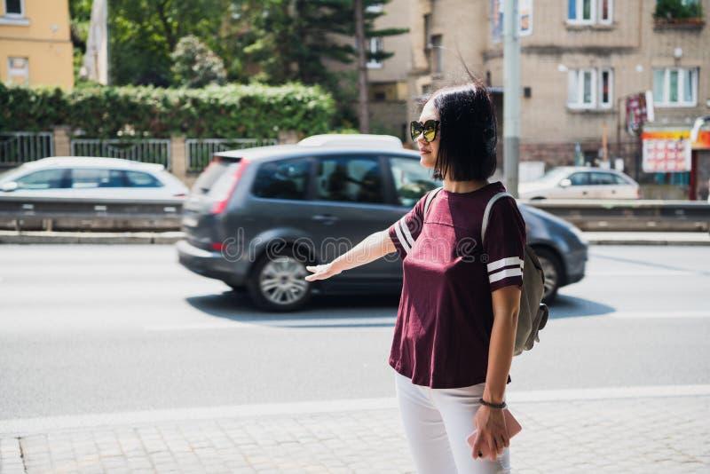 Giovane donna con uno zaino che fa auto-stop su una strada fotografie stock