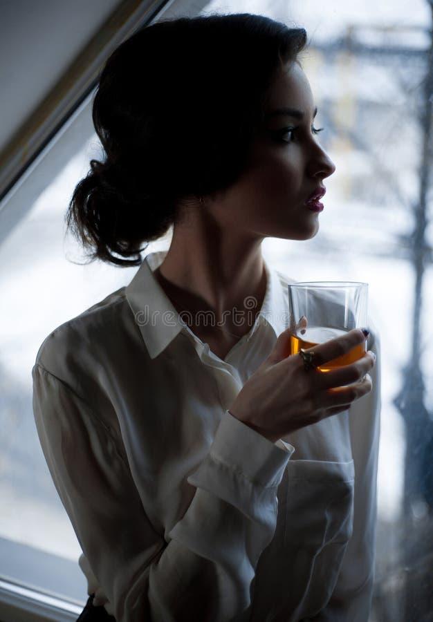 Giovane donna con vetro di whiskey a fondo della finestra fotografia stock libera da diritti