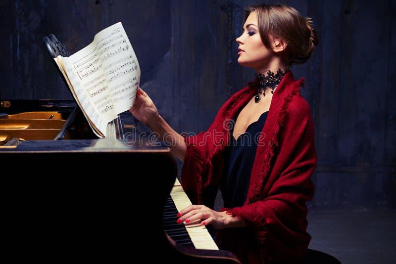 Giovane donna contentissima che gira la partitura con le note mentre p fotografie stock libere da diritti