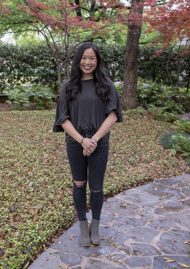 Giovane donna coreana adorabile che posa su un marciapiede a Dallas, il Texas fotografia stock