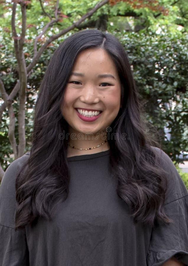 Giovane donna coreana adorabile che posa su un marciapiede a Dallas, il Texas immagini stock