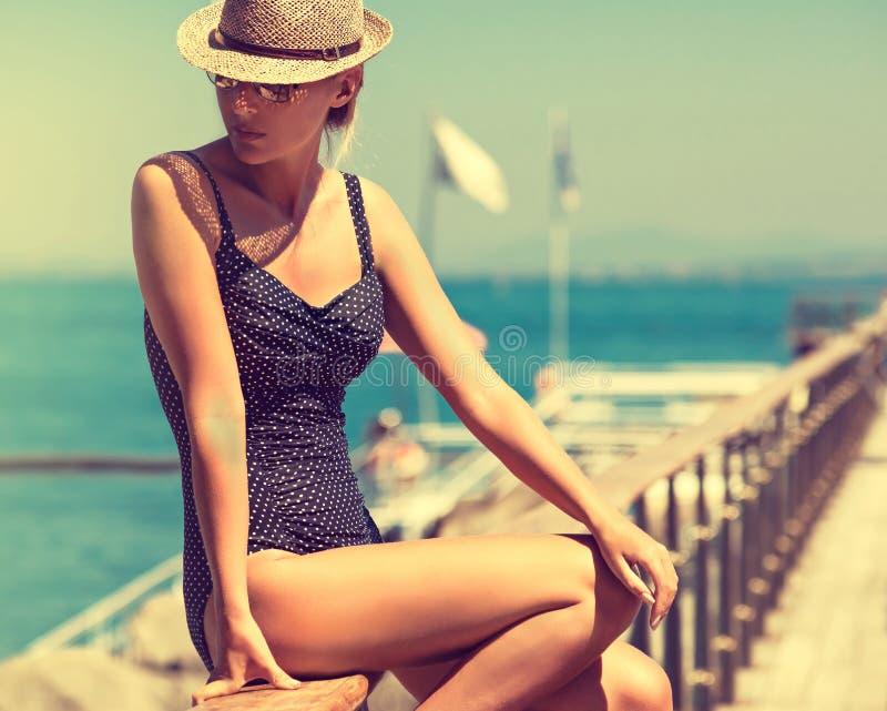 Giovane donna in costume da bagno del bikini e cappello del sole fotografie stock