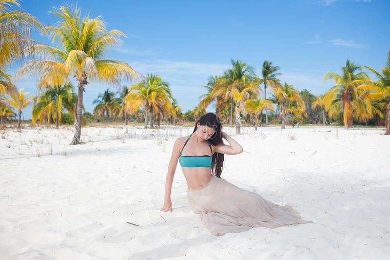Giovane donna in costume da bagno e gonna scorrente, ballanti su una spiaggia caraibica fotografia stock libera da diritti