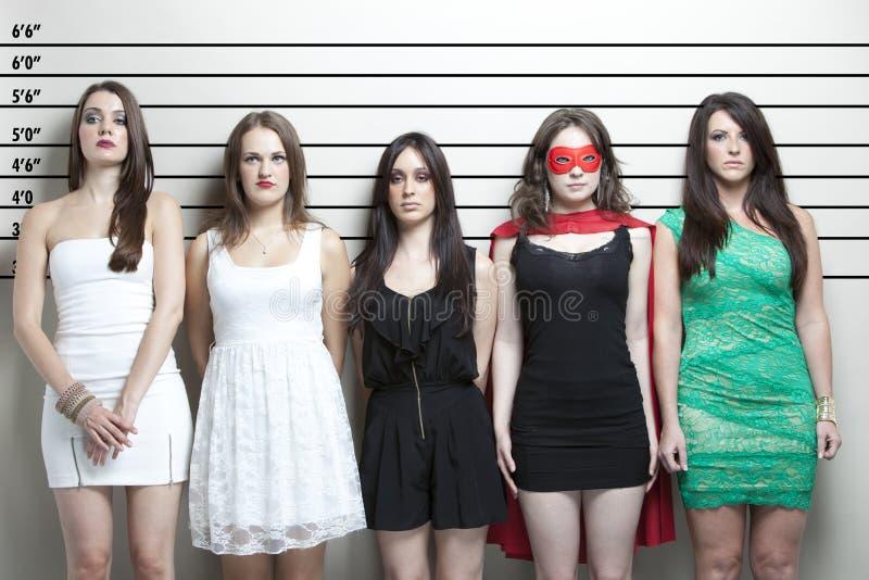 Giovane donna in costume del supereroe con gli amici in un programma della polizia immagini stock