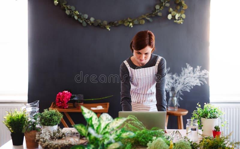 Giovane donna creativa in un negozio di fiore, facendo uso del computer portatile Una partenza dell'affare del fiorista immagine stock