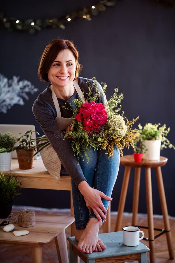 Giovane donna creativa in un negozio di fiore Una partenza dell'affare del fiorista immagini stock libere da diritti