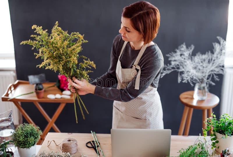 Giovane donna creativa in un negozio di fiore Una partenza dell'affare del fiorista fotografia stock libera da diritti