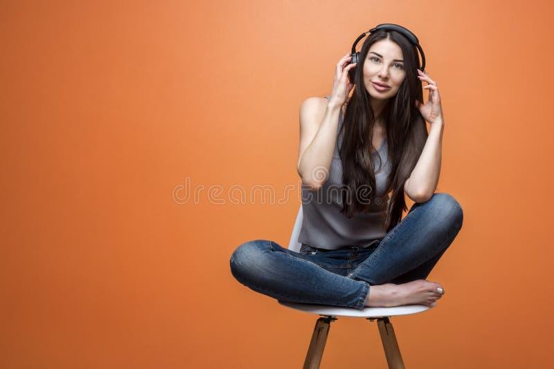 Giovane donna in cuffie che ascolta la musica sulla sedia immagini stock libere da diritti