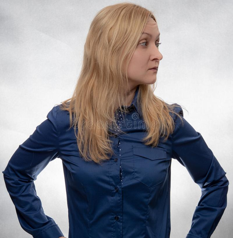 Giovane donna curiosa in camicia blu casuale che sembra giusta fotografia stock libera da diritti