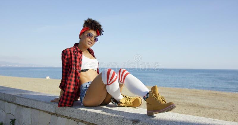 Giovane donna d'avanguardia che si rilassa su una parete fronte mare fotografia stock libera da diritti