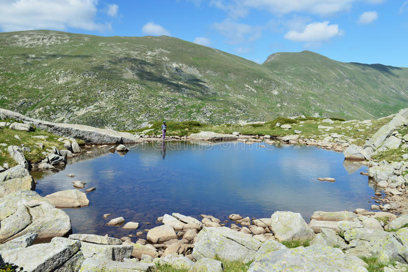 Giovane donna da un lago blu calmo della montagna immagini stock