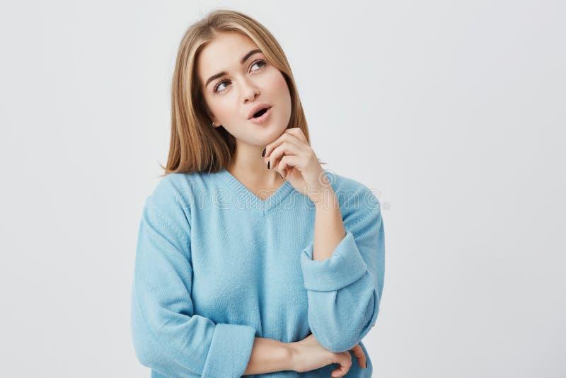 Giovane donna dagli occhi scuri con capelli giusti che portano maglione blu che ha espressione pensierosa che pensa sopra i suoi  fotografia stock