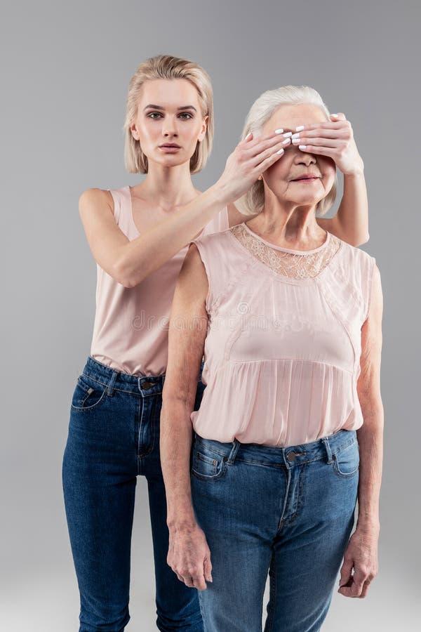 Giovane donna dai capelli corti risoluta che riguarda visione di sua madre fotografia stock