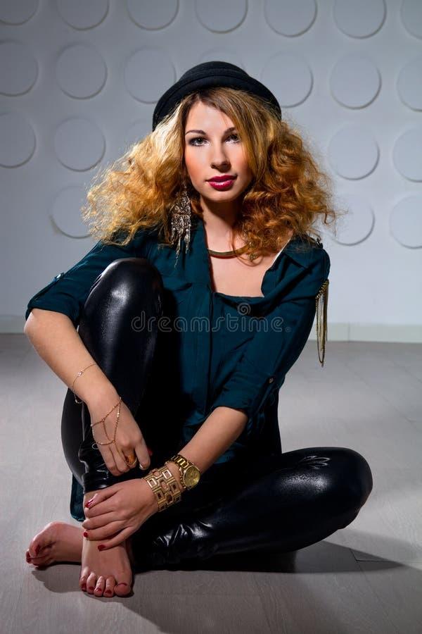 Giovane donna dai capelli rossi che si siede sul pavimento fotografia stock libera da diritti