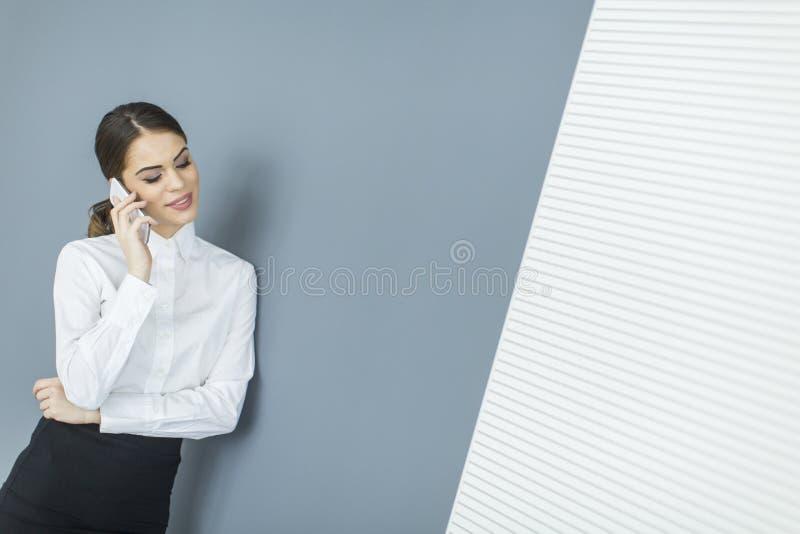 Download Giovane donna dalla parete fotografia stock. Immagine di casuale - 55360882