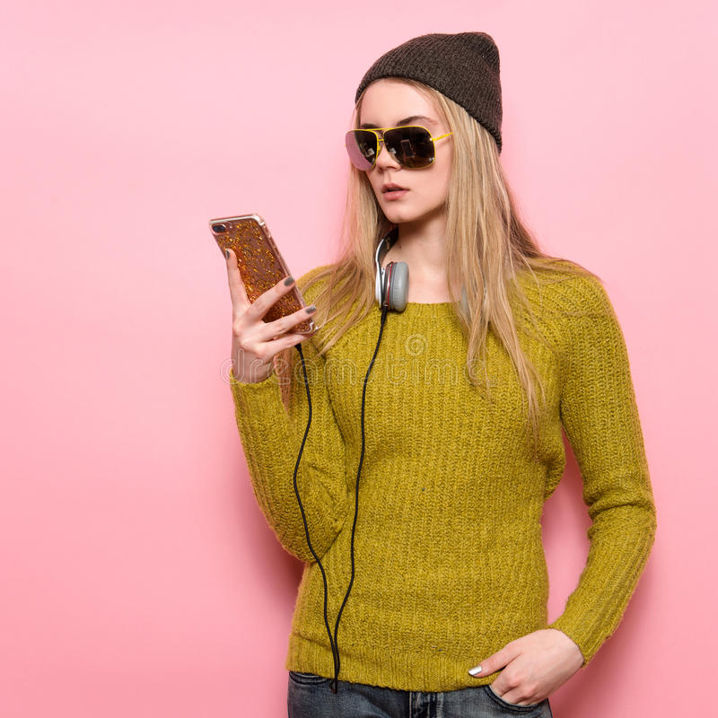 Giovane donna dei pantaloni a vita bassa che per mezzo del telefono cellulare e selezionando musica per ascoltare sulle cuffie immagini stock