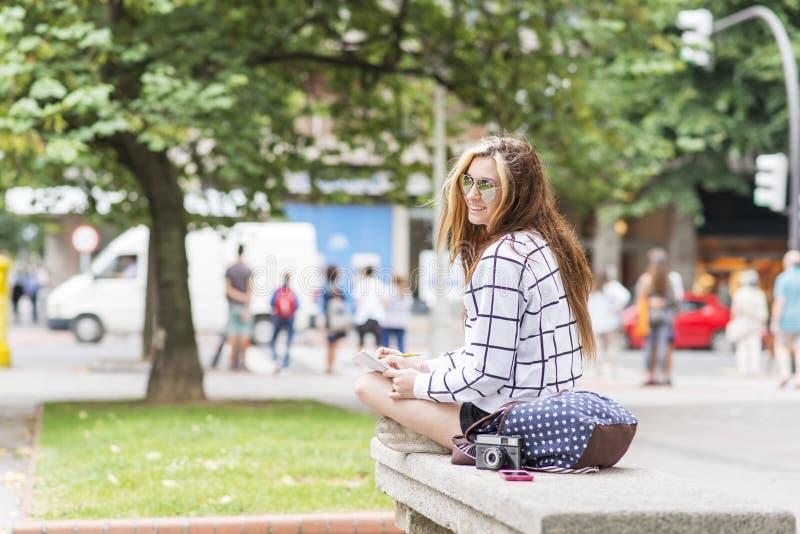 Giovane donna dei pantaloni a vita bassa che viaggia e che prende le note nello stret immagini stock libere da diritti