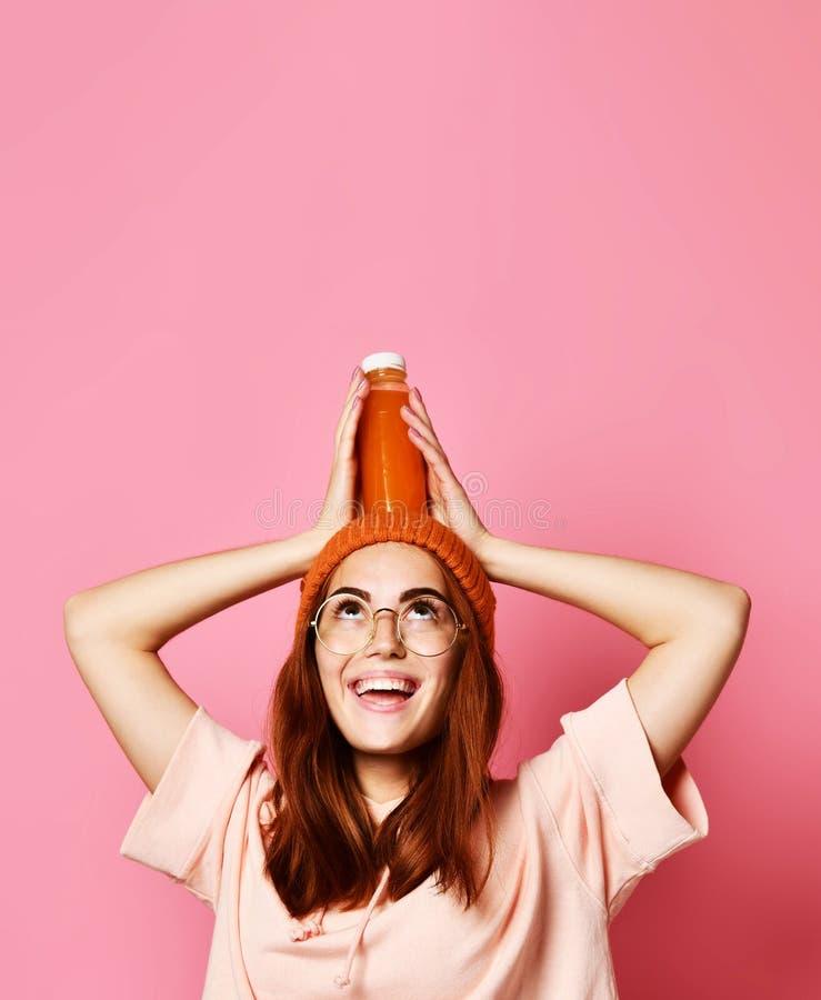 Giovane donna dei pantaloni a vita bassa con capelli ricci in occhiali da sole che beve succo d'arancia fresco dalla bottiglia, s fotografie stock libere da diritti